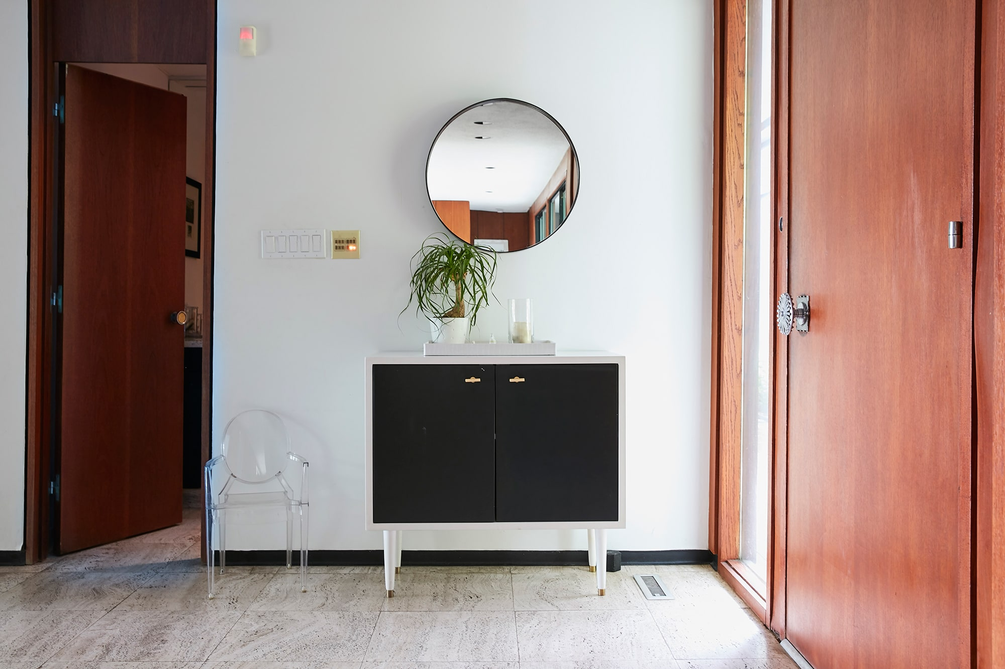 mid-century modern entryway with mirror and door