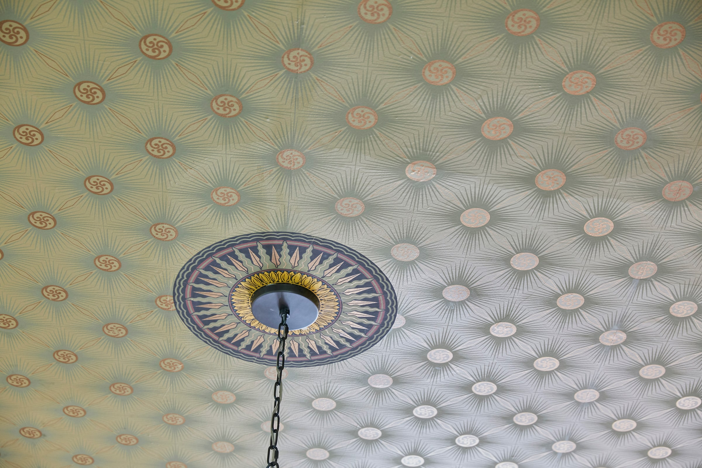 detail of patterned ceiling paper and light fixture